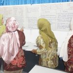 Participants share their prior knowledge on integrated thematic learning during a poster presentation session.